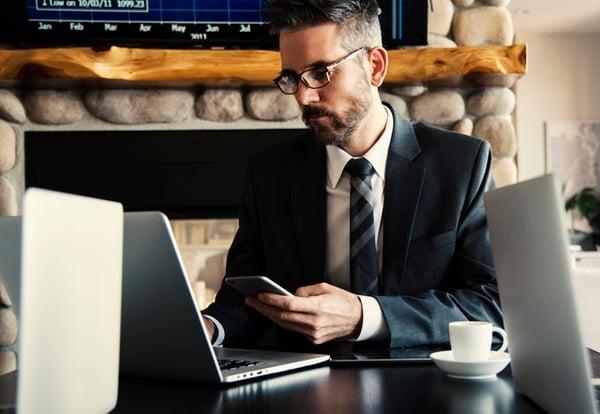 man checking his phone and computer